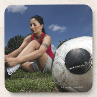 portrait of female football player tying her beverage coaster