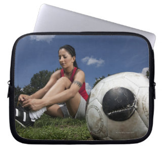 portrait of female football player tying her laptop sleeve