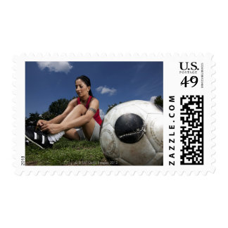 portrait of female football player tying her postage stamp