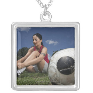portrait of female football player tying her silver plated necklace