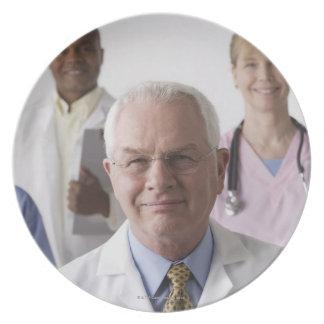 Portrait of four medical professionals, studio party plate