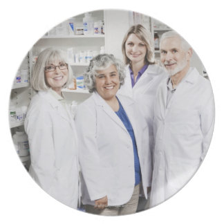 Portrait of four smiling pharmacists dinner plate