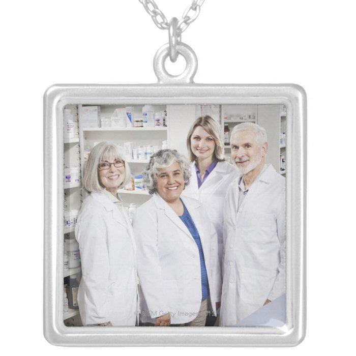 Portrait of four smiling pharmacists silver plated necklace