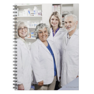Portrait of four smiling pharmacists spiral notebook