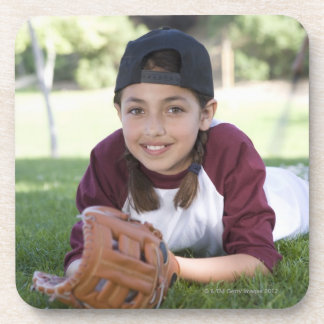 Portrait of girl lying on ground with baseball drink coaster