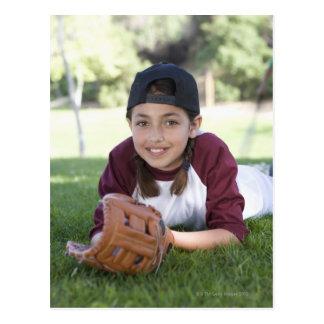Portrait of girl lying on ground with baseball postcard