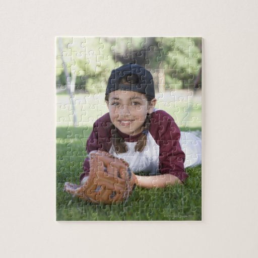 Portrait of girl lying on ground with baseball puzzle