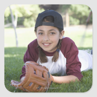 Portrait of girl lying on ground with baseball square sticker