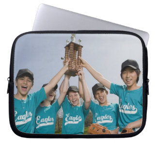 Portrait of little league players with trophy computer sleeves