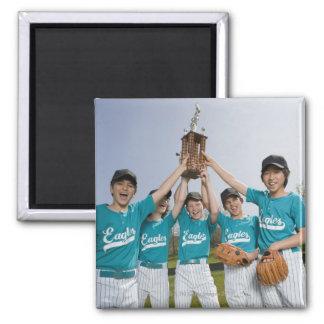 Portrait of little league players with trophy magnet