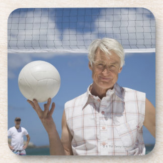 Portrait of mature man holding volley ball on drink coasters