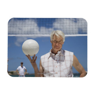 Portrait of mature man holding volley ball on magnet