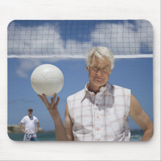 Portrait of mature man holding volley ball on mouse pad