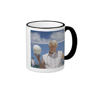 Portrait of mature man holding volley ball on mug