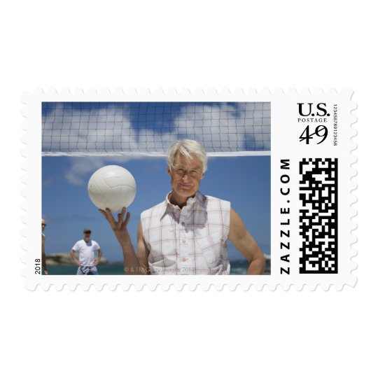 Portrait of mature man holding volley ball on postage