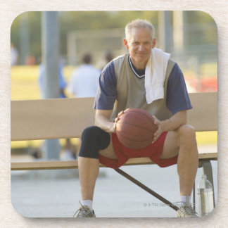 Portrait of mature man with basketball sitting drink coaster