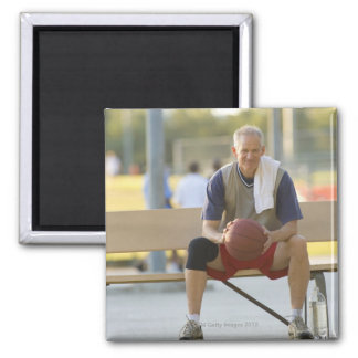 Portrait of mature man with basketball sitting magnet