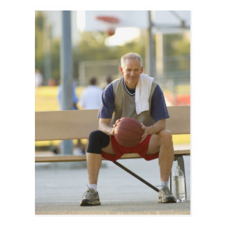 Portrait of mature man with basketball sitting postcard