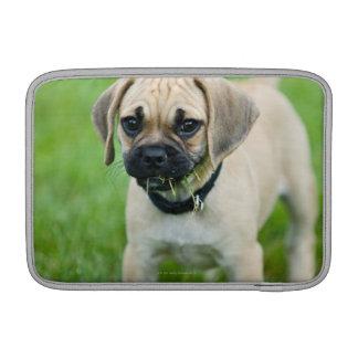 Portrait of puppy standing in grass MacBook sleeve