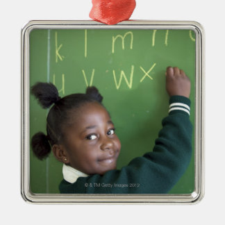 Portrait of smiling schoolgirl writing on the metal ornament