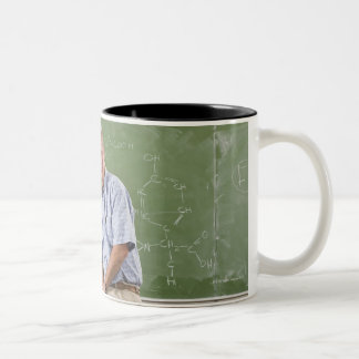 Portrait of teacher sitting on desk in front of Two-Tone coffee mug