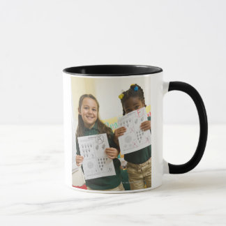 Portrait of two preschool girls with A plus and Mug