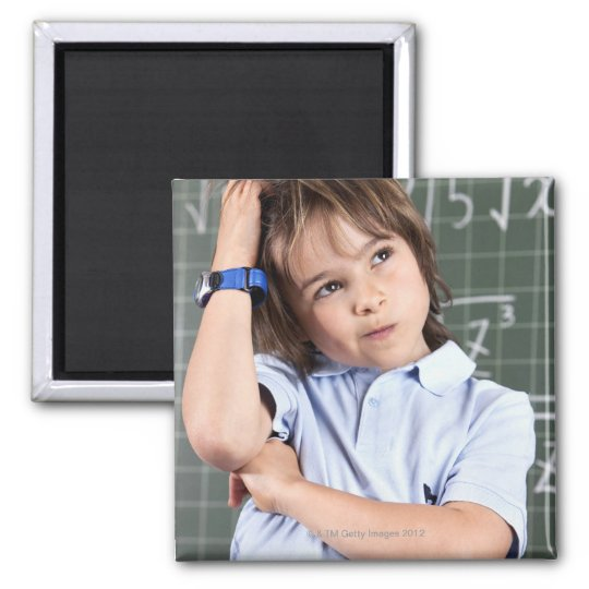 portrait of young boy in classroom in front pof magnet