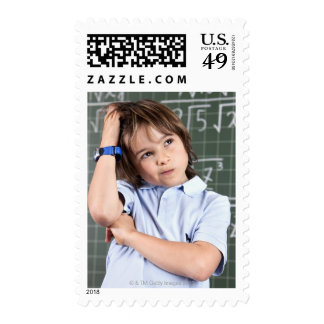 portrait of young boy in classroom in front pof postage