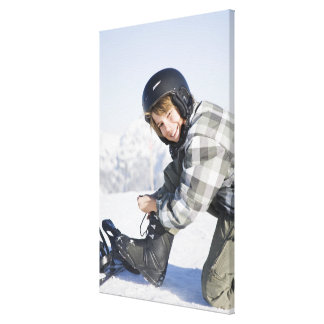Portrait of young boy kneeling to tie ski boot, canvas print