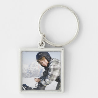 Portrait of young boy kneeling to tie ski boot, keychain