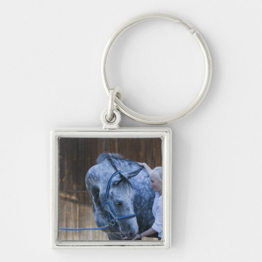 portrait of young girl holding white horse keychain