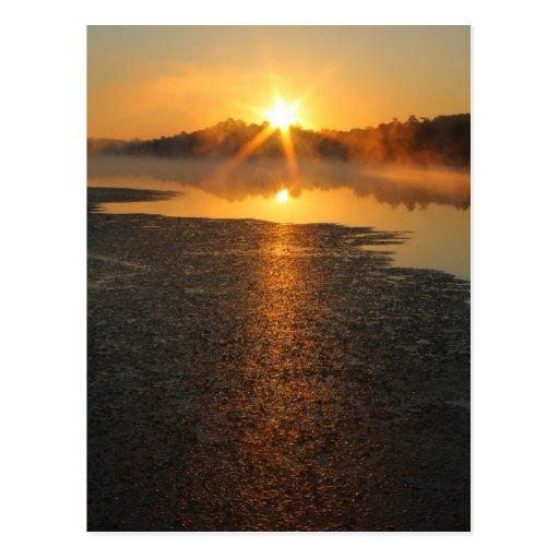 Postal brumosa de la salida del sol del lago