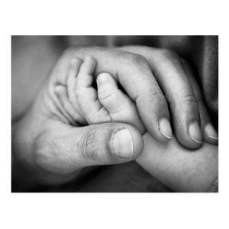 Postal de la mano del bebé en mano de los padres