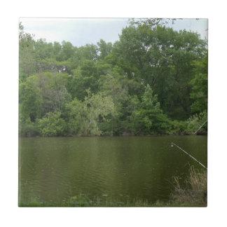 Poste de la pesca que descansa delante de un lago tejas  cerámicas
