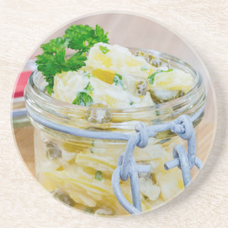 Potato salad in a jar on wooden coaster