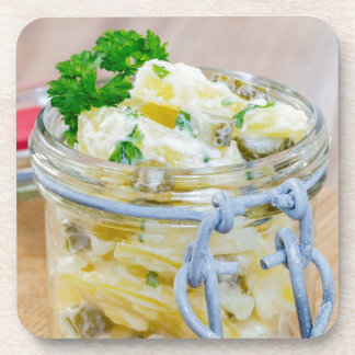 Potato salad in a jar on wooden drink coaster