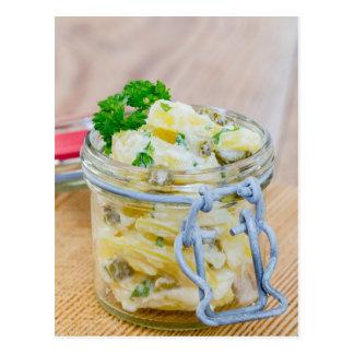 Potato salad in a jar on wooden postcard