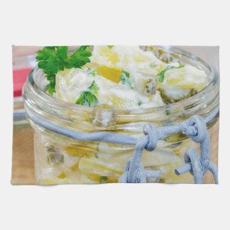 Potato salad in a jar on wooden towel