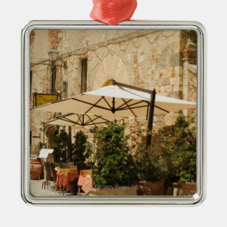 Potted plants and patio umbrellas in front of a christmas ornament
