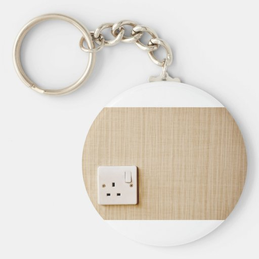 Power outlet at the corner of a wall basic round button keychain