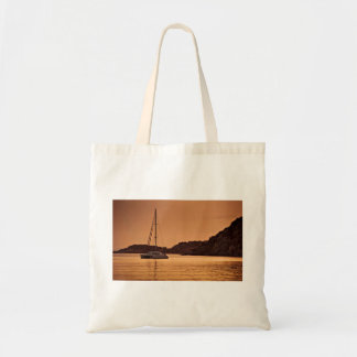 Powerful boat near shore of rocky hills budget tote bag