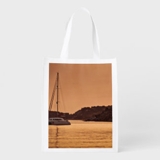 Powerful boat near shore of rocky hills grocery bag