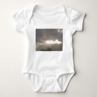 powerful sun peeks through baby bodysuit