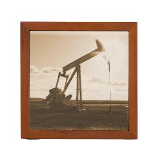Pozo de petróleo que bombea en la puesta del sol organizador de escritorio