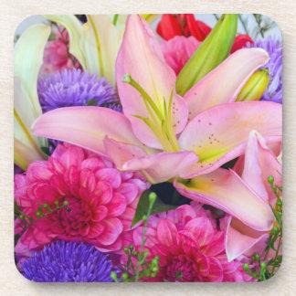 Práctico de costa rosado de las flores del lirio y posavasos de bebidas