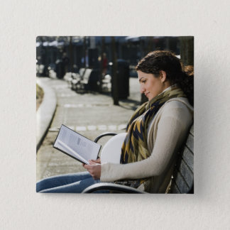 Pregnant Middle Eastern woman reading on park Button
