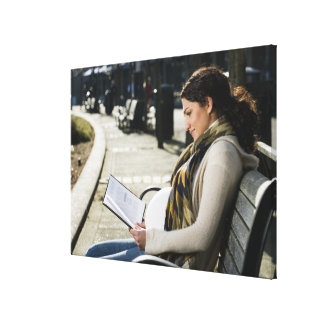 Pregnant Middle Eastern woman reading on park Canvas Print