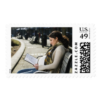 Pregnant Middle Eastern woman reading on park Postage