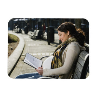 Pregnant Middle Eastern woman reading on park Rectangular Photo Magnet