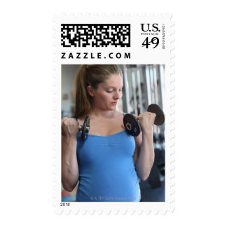 pregnant woman exercising at health club postage
